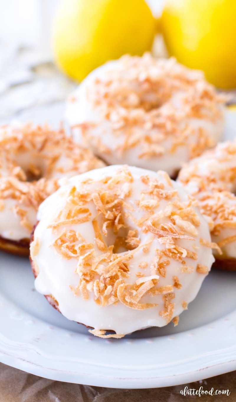 These easy lemon donuts are baked in the oven and topped with a lemon glaze and toasted coconut for a sweet breakfast treat! lemon coconut dessert, lemon donuts, coconut donuts, lemon bread
