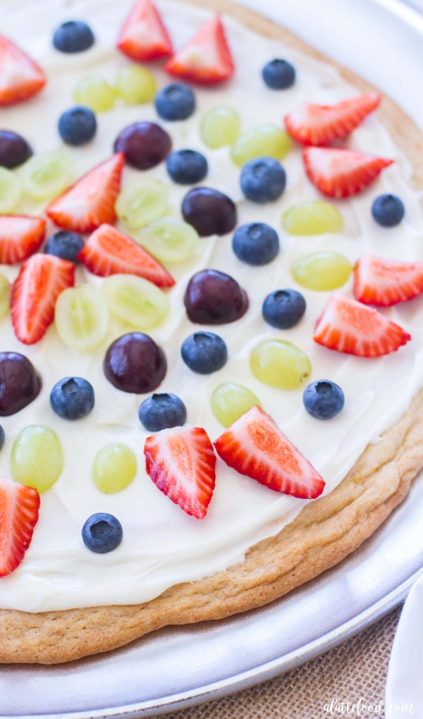 This easy lemon sugar cookie fruit pizza is made with a cookie mix, topped with a creamy marshmallow frosting, and layered with fresh fruit!