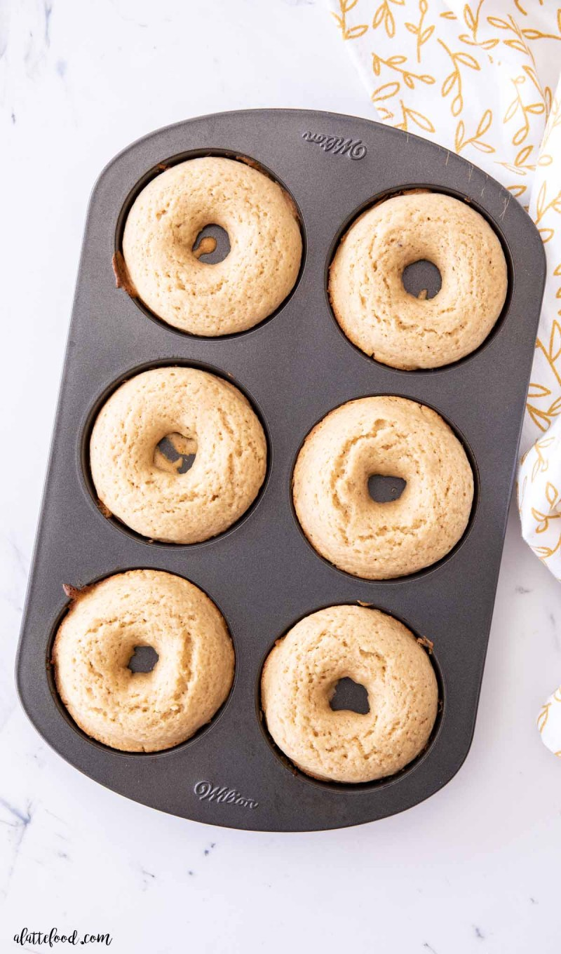 baked donuts in a donut pan on a white marble board
