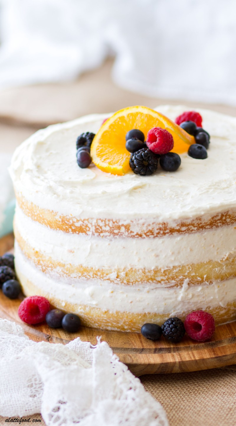 This Mixed Berry Orange Naked Cake is light, fluffy, and filled with a creamy orange whipped cream cheese frosting. This pretty homemade naked cake is an orange cake with fresh berries between the layers and on top, making this the perfect spring dessert! naked cake, orange cake, berry cake, cake