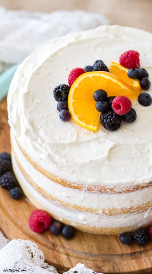 This Mixed Berry Orange Naked Cake is light, fluffy, and filled with a creamy orange whipped cream cheese frosting. This pretty homemade naked cake is an orange cake with fresh berries between the layers and on top, making this the perfect spring dessert!