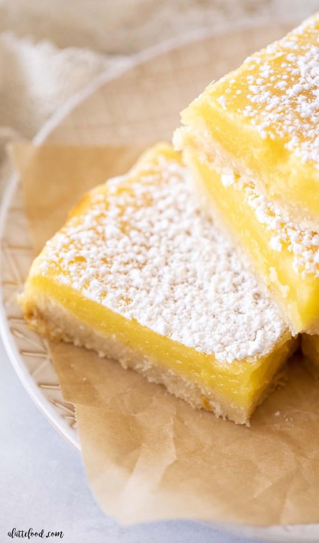 powdered sugar lemon bars on brown parchment paper