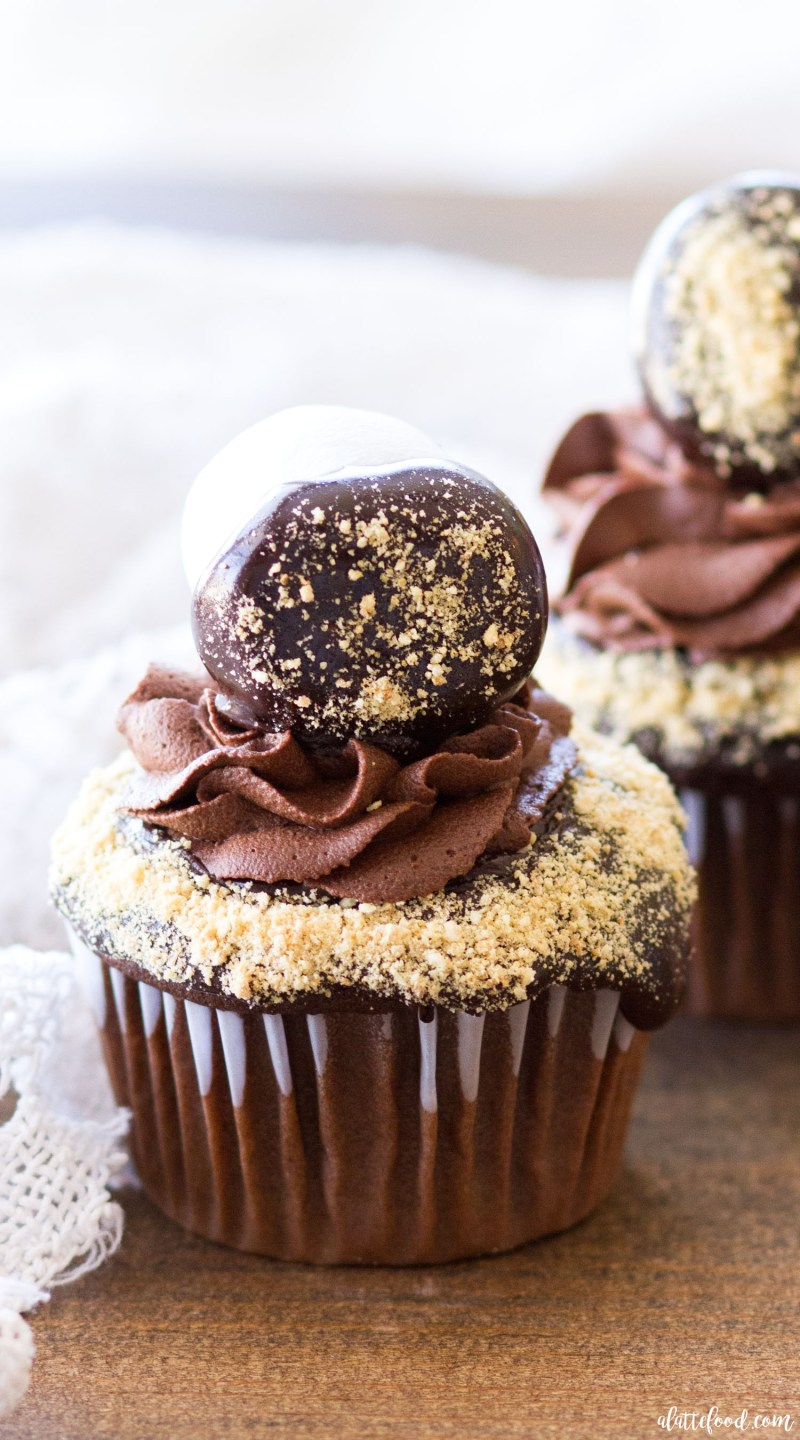 These ridiculously rich Chocolate S'mores Cupcakes begin with a chocolate cupcake base, have a marshmallow center, and are frosted with homemade chocolate ganache frosting. Graham cracker crumbs, extra ganache, and chocolate ganache covered marshmallows complete these s'more cupcakes! Summer dessert has never looked better! s'mores, s'more cupcakes, best chocolate cupcake recipe, how to make ganache frosting