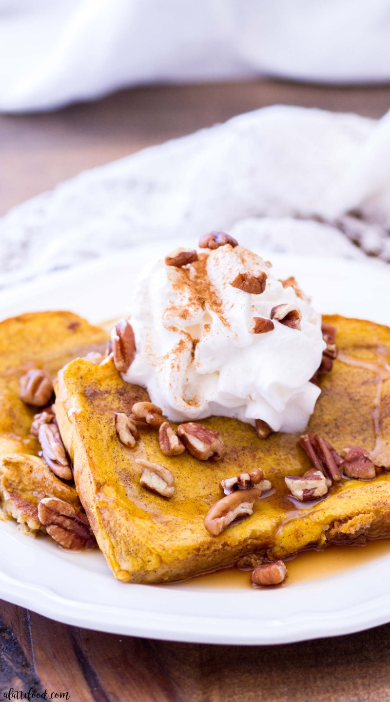 This Easy Pumpkin French Toast Recipe is baked in the oven, making this the perfect fall breakfast! This Baked Pumpkin French Toast Recipe uses thick-cut bread, and is soaked in a rich pumpkin custard and baked to perfection!