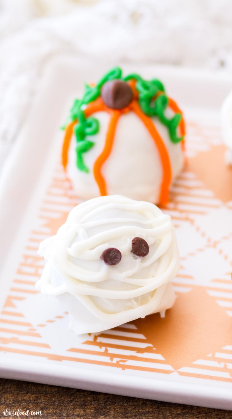 These adorable Halloween Cookie Truffles are so fun for fall! Cookies and cream cheese get mix together to make the filling of each truffle. When dipped in white almond bark and decorated for Halloween, these easy cookie truffles are sure to be a Halloween dessert favorite!
