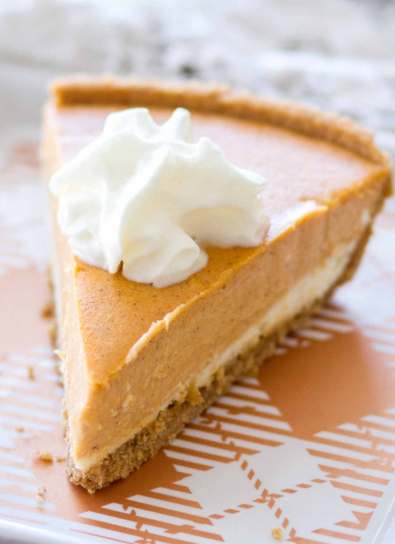 This homemade Pumpkin Cheesecake Recipe is gluten-free! A layer of vanilla cheesecake, a layer of spiced pumpkin cheesecake, and a pinch of whipped cream make this super simple pumpkin cheesecake that is a holiday dessert favorite!