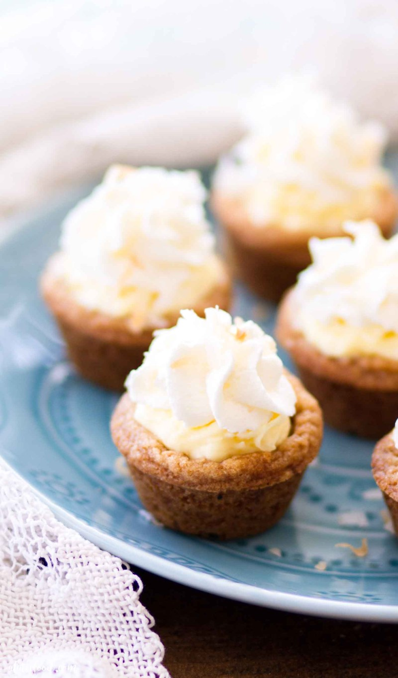 four cookie cups filled with coconut cream and topped with whipped cream