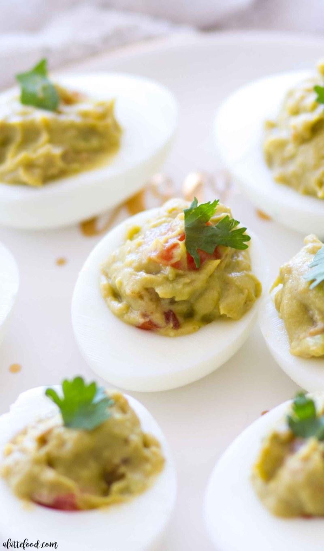 guacamole deviled eggs on white plate