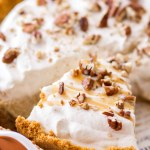 A slice of Pecan Caramel Cheesecake with homemade caramel whipped cream and chopped pecans.