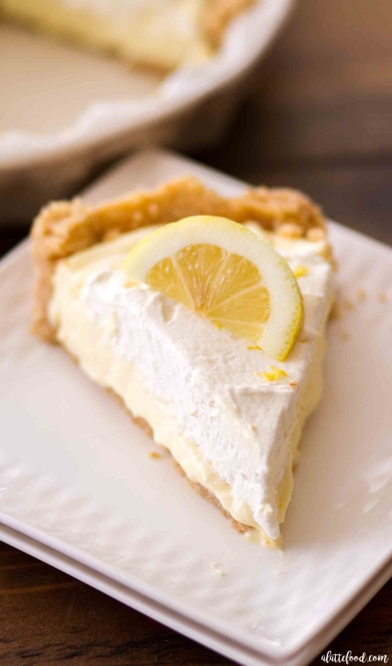 This slice of no bake lemon cream pie is topped with homemade lemon whipped cream and in an oreo vanilla wafer crust.