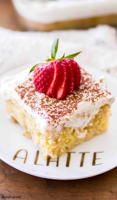 This easy tiramisu poke cake slice is topped with fresh strawberries and cream.