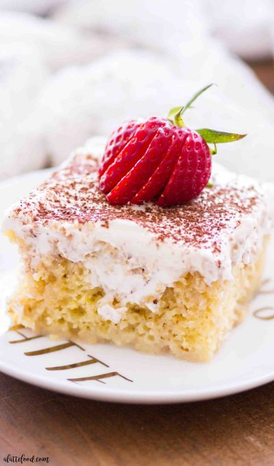 This tiramisu poke cake is soaked with a coffee cream, topped with whipped cream frosting, and each slice is served on a white plate with fresh strawberries.