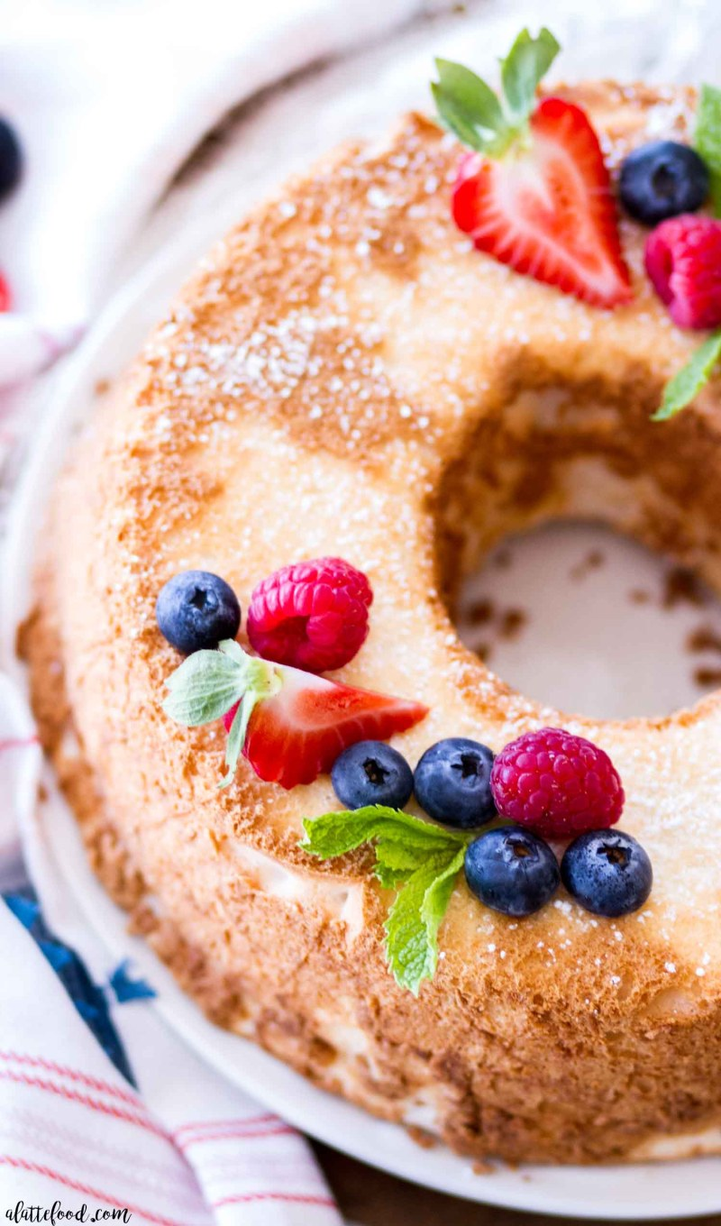 angel food cake with fresh berries and mint on white plate