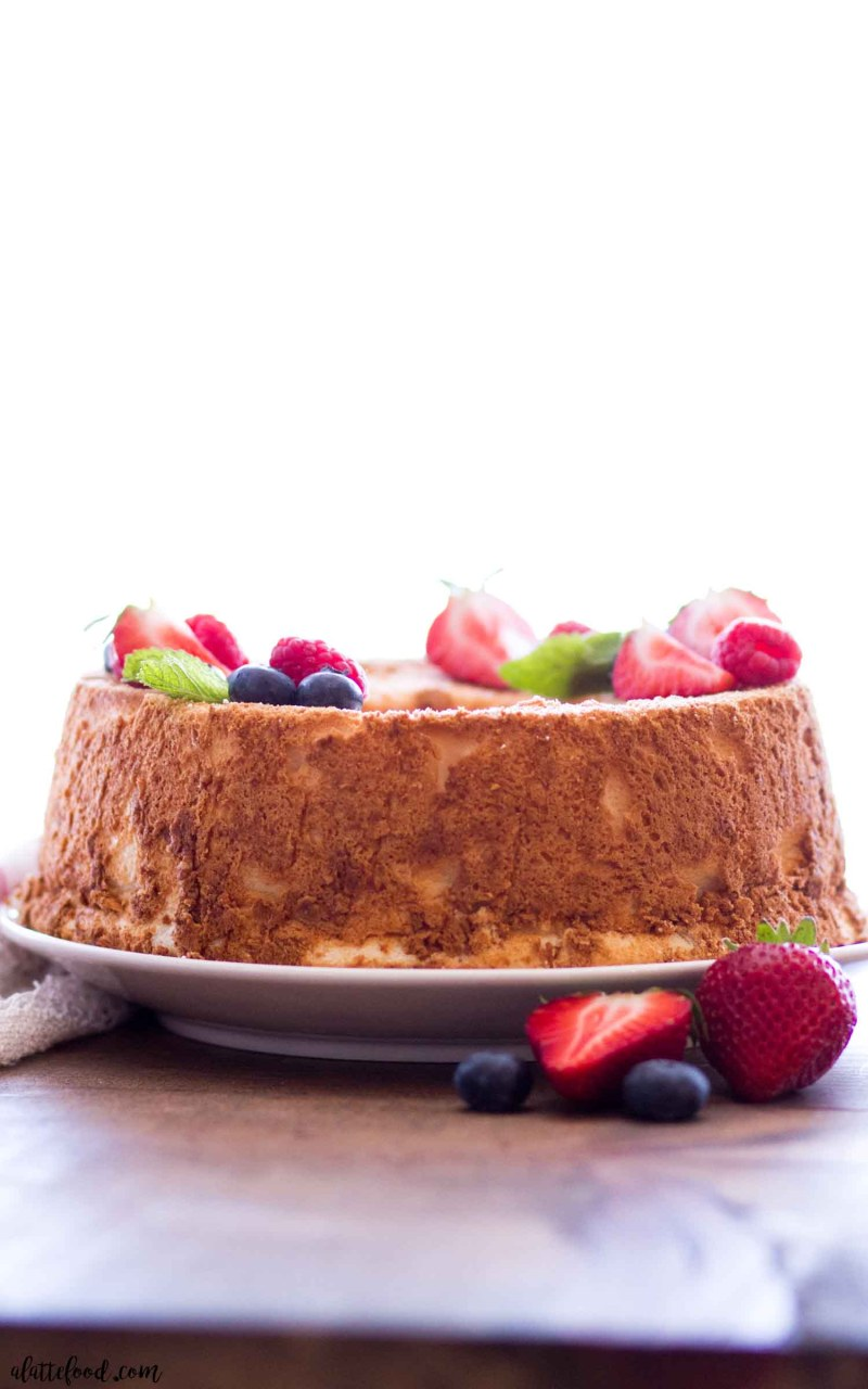 airy angel food cake recipe with berries and fresh mint on brown cutting board