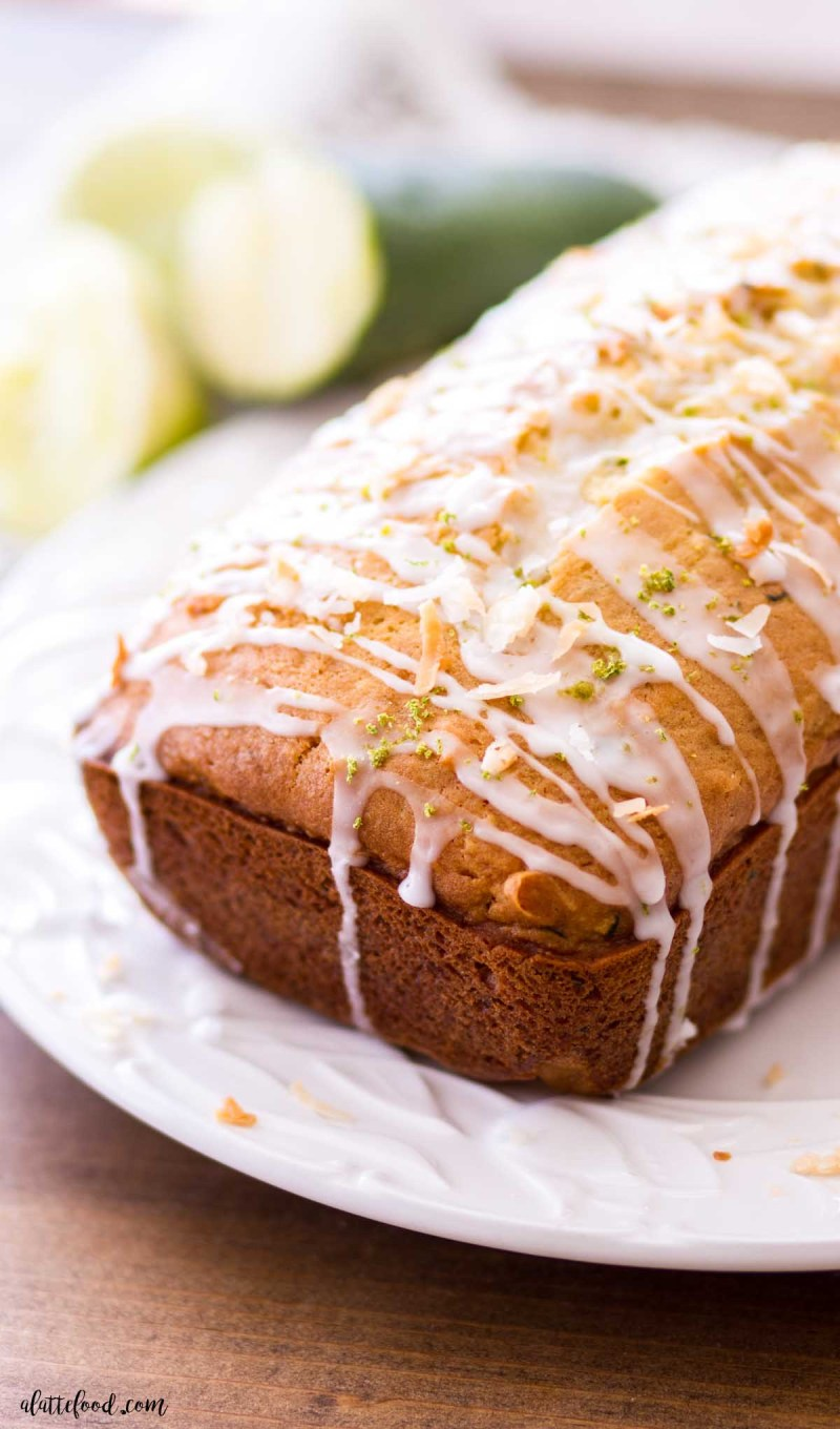loaf of lime glazed zucchini bread with toasted coconut on white plate