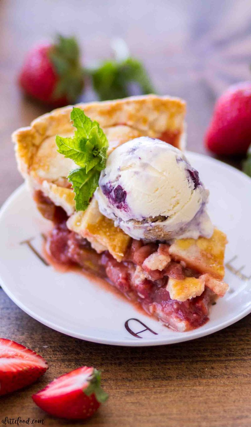 A slice of homemade strawberry rhubarb pie with a scoop of ice cream