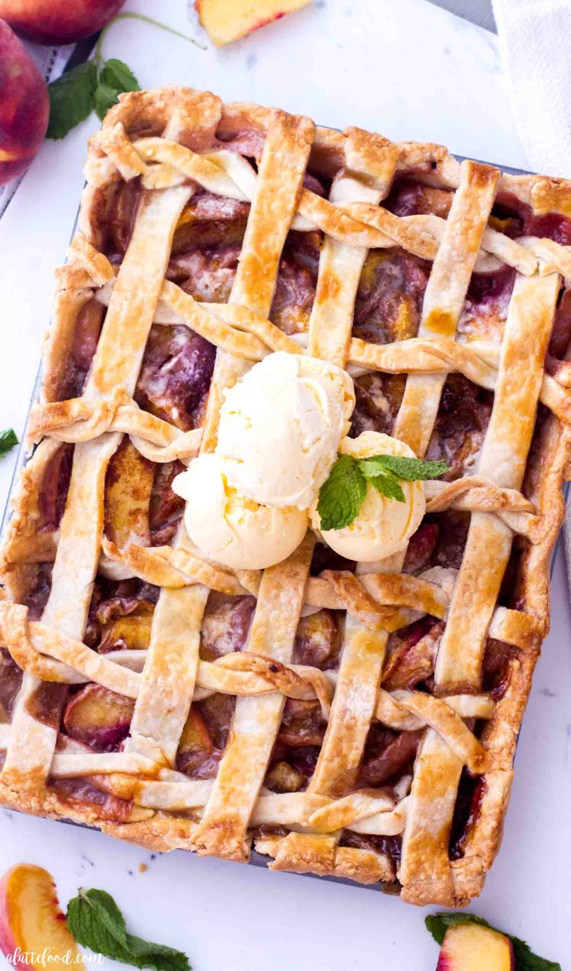 Fresh Peach Slab Pie topped with ice cream and a lattice crust.