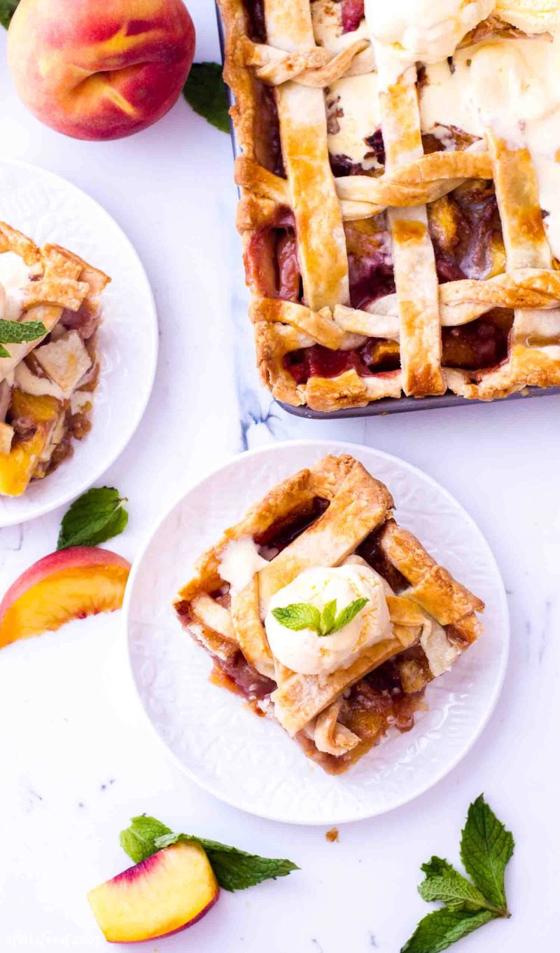 A slice of homemade peach pie with fresh peaches topped with ice cream is the best summer can offer!