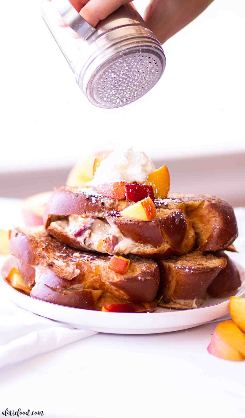 The best peach cheesecake stuffed french toast topped with powdered sugar