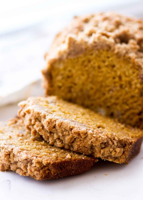 slice of pumpkin bread with brown sugar streusel on white cutting board