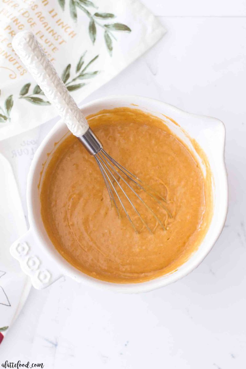 pumpkin poke cake batter in a white mixing bowl