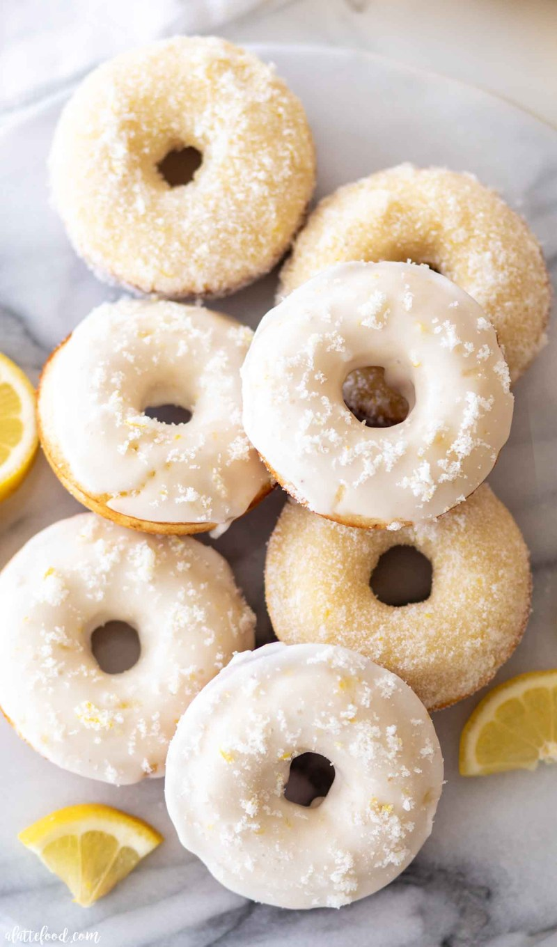 baked lemon donuts stacked on a marble board