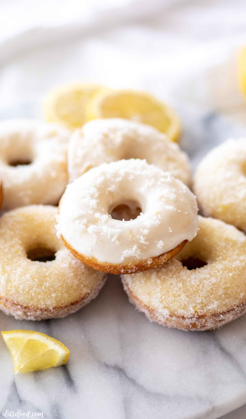 homemade lemon donuts baked and stacked on cutting board