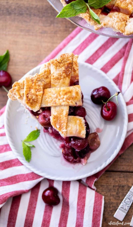 cherry pie slice with lattice crust on striped towel
