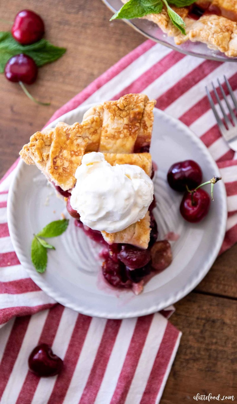 sweet cherry pie with a scoop of ice cream on gray plate