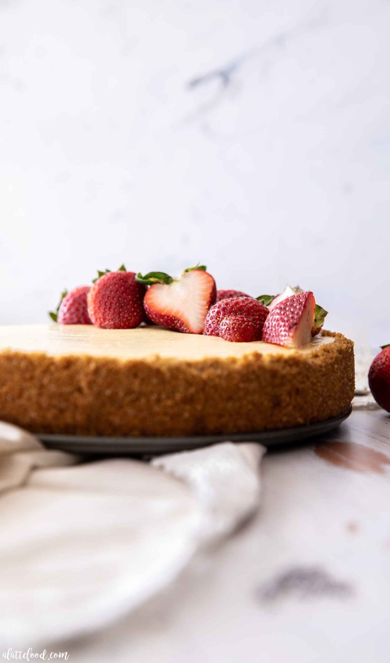 strawberry cheesecake with graham cracker crust on wooden board