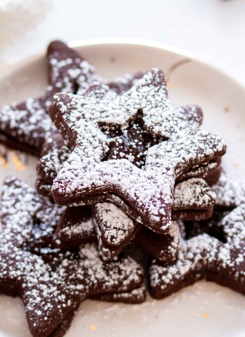 Jam Chocolate Sugar Cookies on a gold and white plate with powdered sugar on top