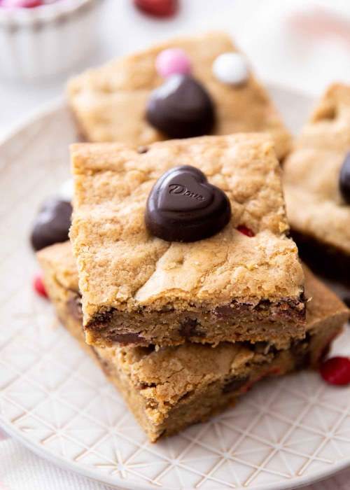 two stacked M&M chocolate chip cookie bars on a cream plate