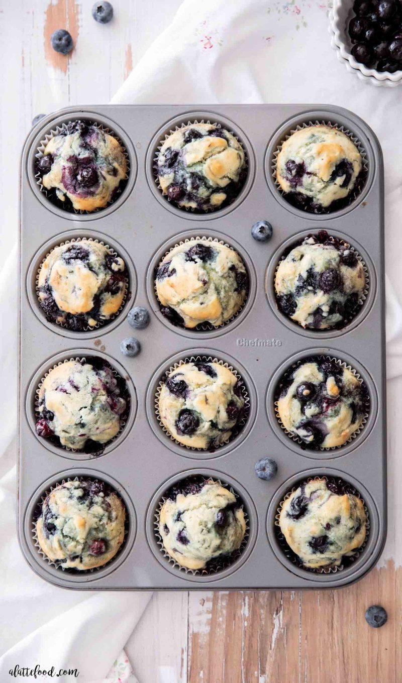sour cream blueberry muffins baked in a metal muffin tin