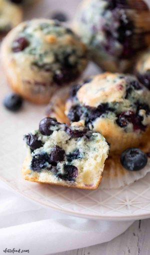 fluffy blueberry muffin cut in half on a white plate with other muffins