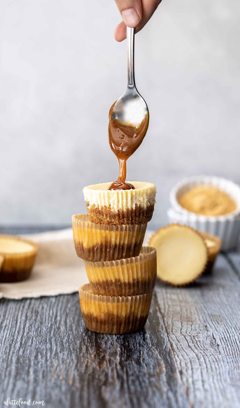 stack of mini cheesecakes with spoon drizzling caramel