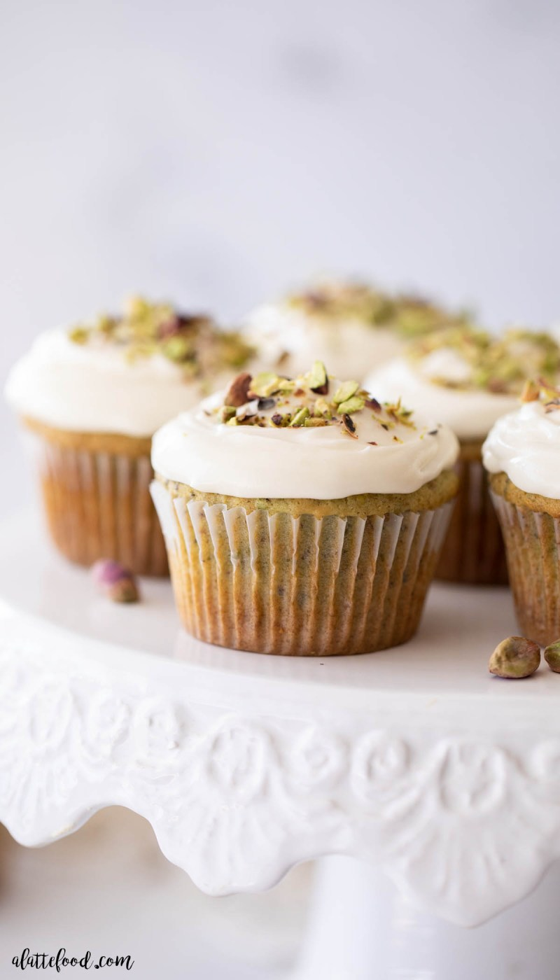 honey pistachio cupcakes with cream cheese frosting on cake stand