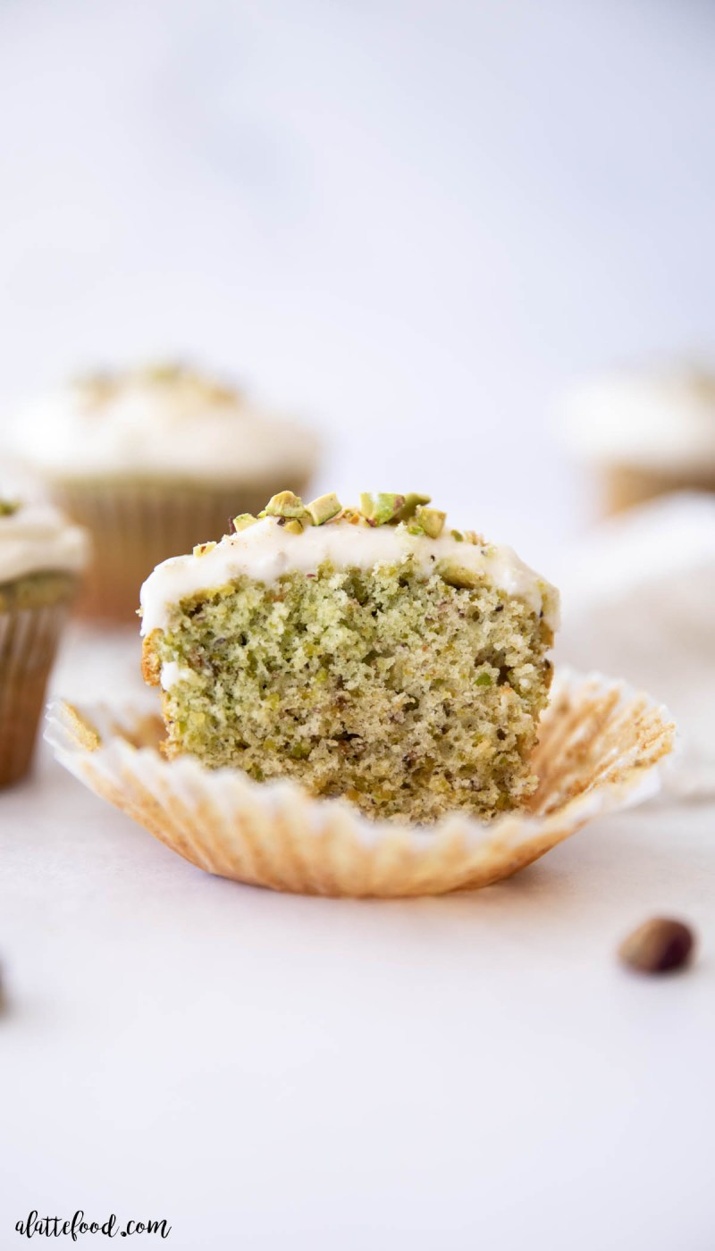 cream cheese frosted pistachio honey cupcake cut in half