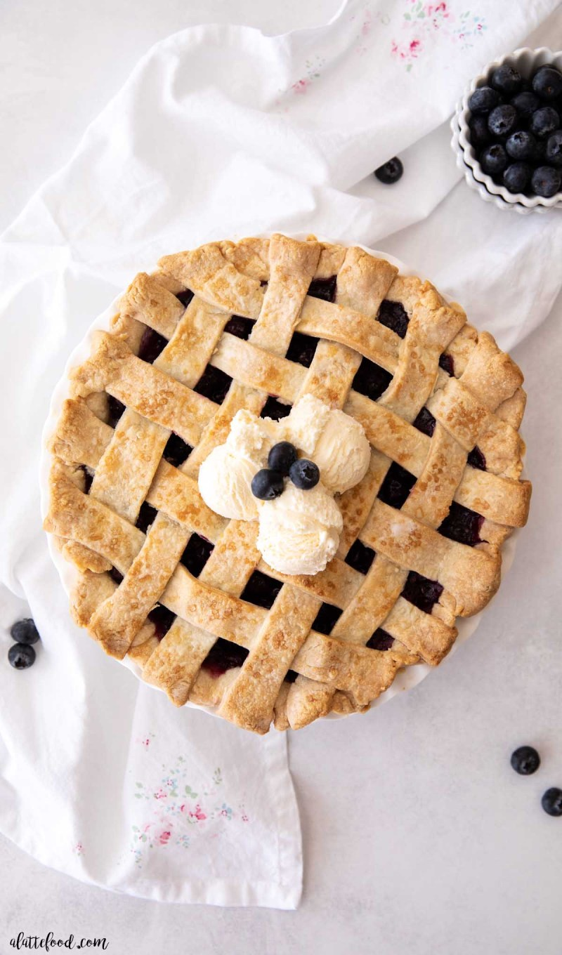 baked homemade blueberry pie with a lattice crust with ice cream and blueberries on top