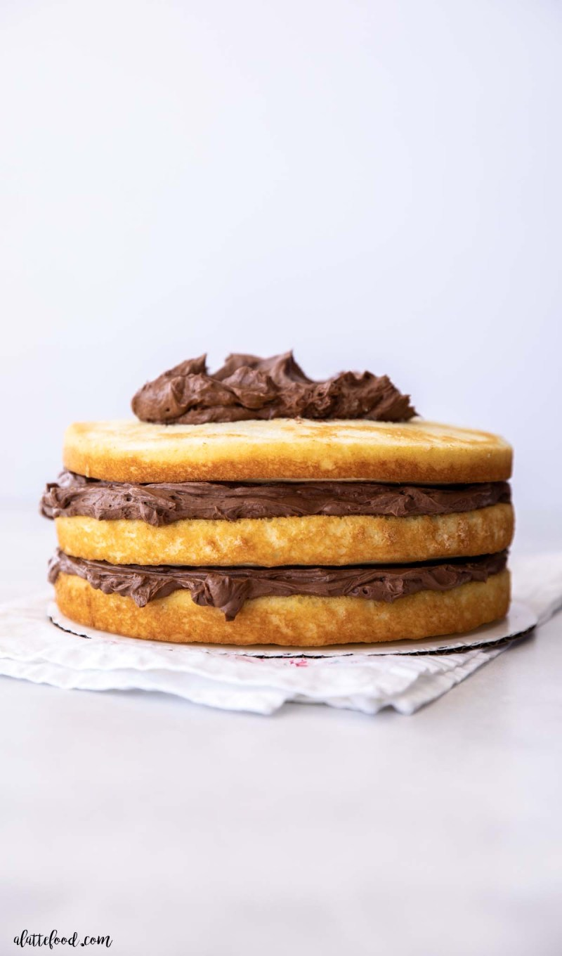 fluffy yellow naked cake with chocolate frosting in the layers