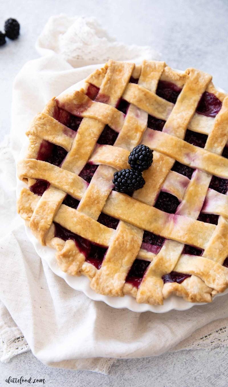 lattice topped fresh blackberry pie in white pie dish