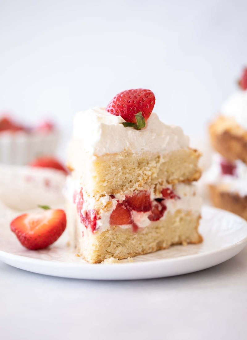 strawberry shortcake cake slice on a white plate with sliced strawberries