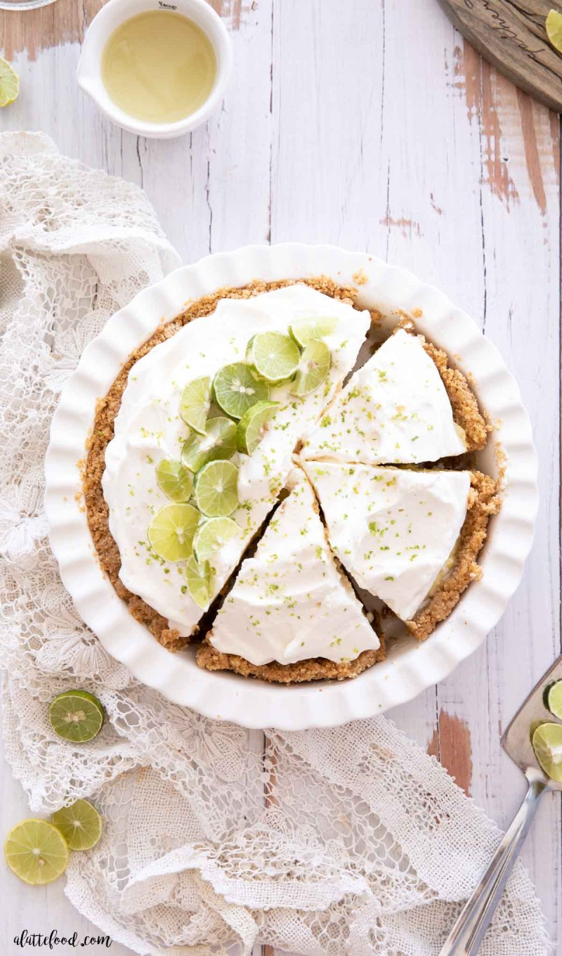 key lime custard pie with whipped cream cut in slices in a white pie plate