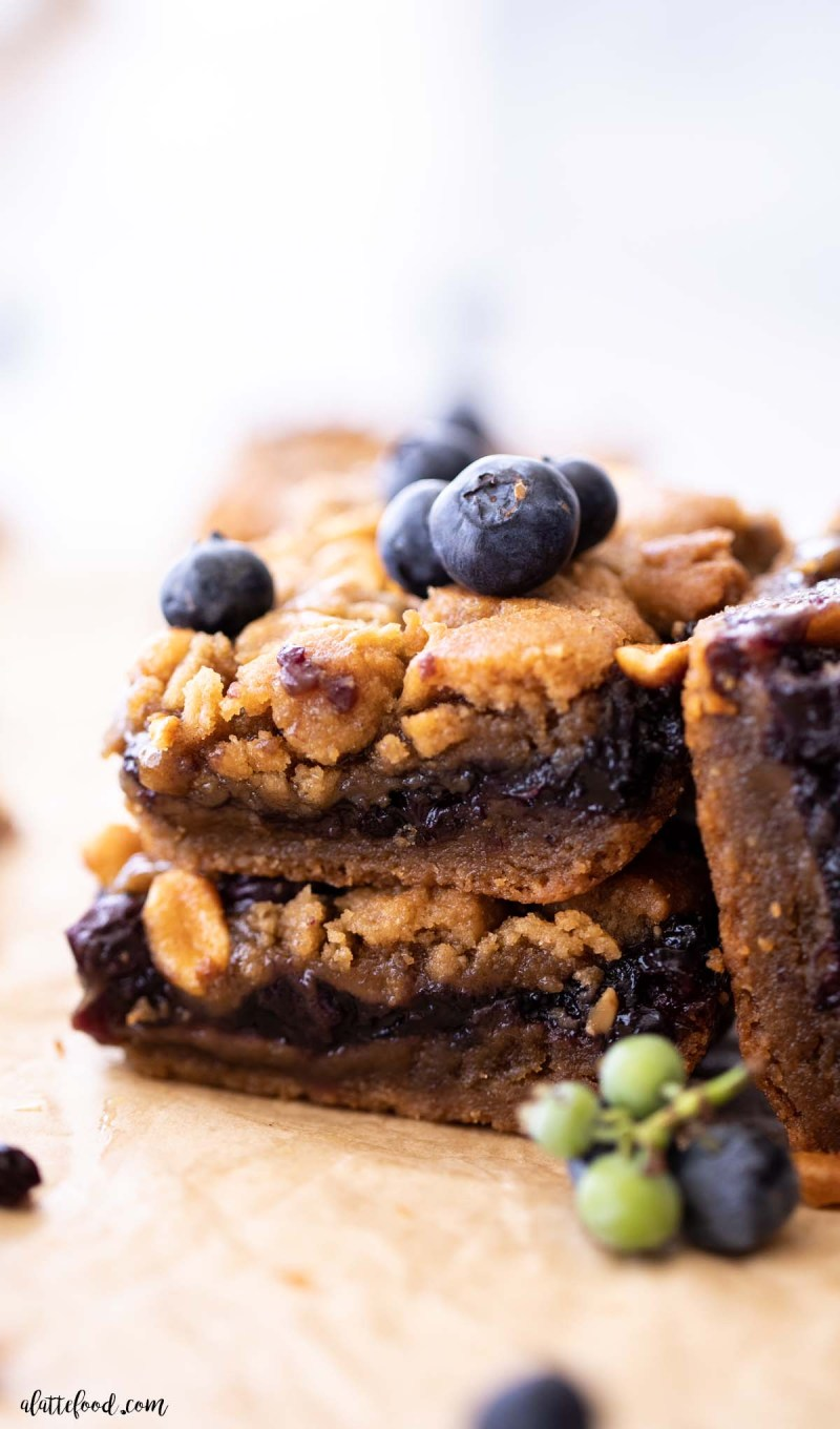 Peanut Butter and Jelly Bars with peanut butter cookie dough and blueberry jam on brown parchment paper
