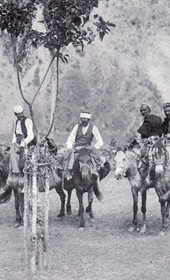 "Jäckh066: ""The men who accompanied me from Prizren through the valley of the Drin. On the left and right are soldiers. The kiradji [horse driver] is in front holding my horse. Behind the tree is Nicola and beside him the son of the Turkish hadji as well as two Albanians in wooden saddles who joined us on the road"" (Photo: Ernst Jäckh, ca. 1910)."