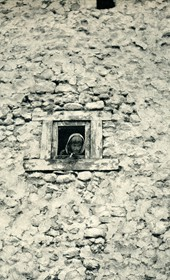 GM043: Child staring out a window in Theth (Photo: Giuseppe Massani, 1940).