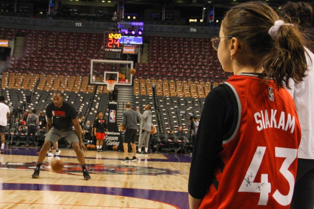 Kawhi Leonard calienta en el Scotiabank Arena ante la atenta mirada de una niña con la camiseta de Pascal Siakam | Alejandro Gaitán