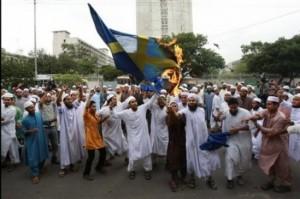 Musulmanes integristas quedan una bandera de Suecia en Malmö.