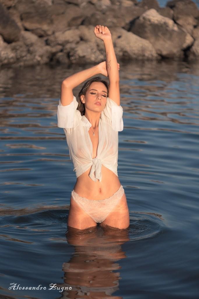 Foto al mare di ragazza con camicetta bianca trasparente