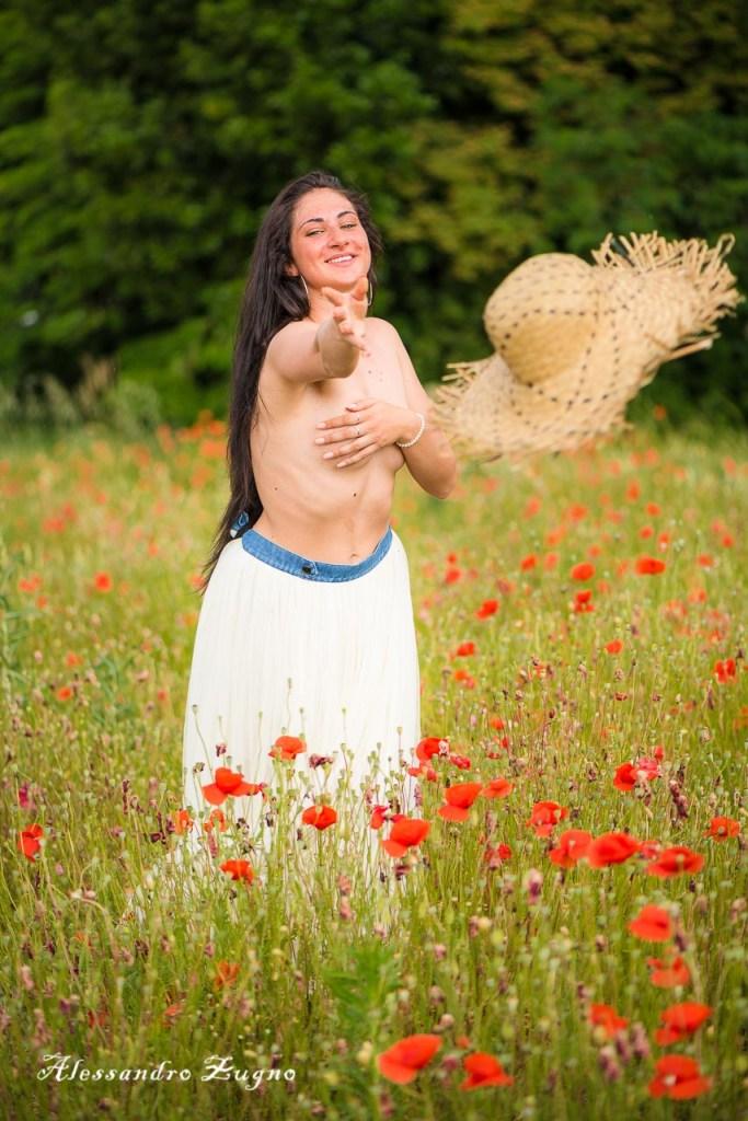 ragazza che lancia cappello di paglia in un campo di papaveri rossi