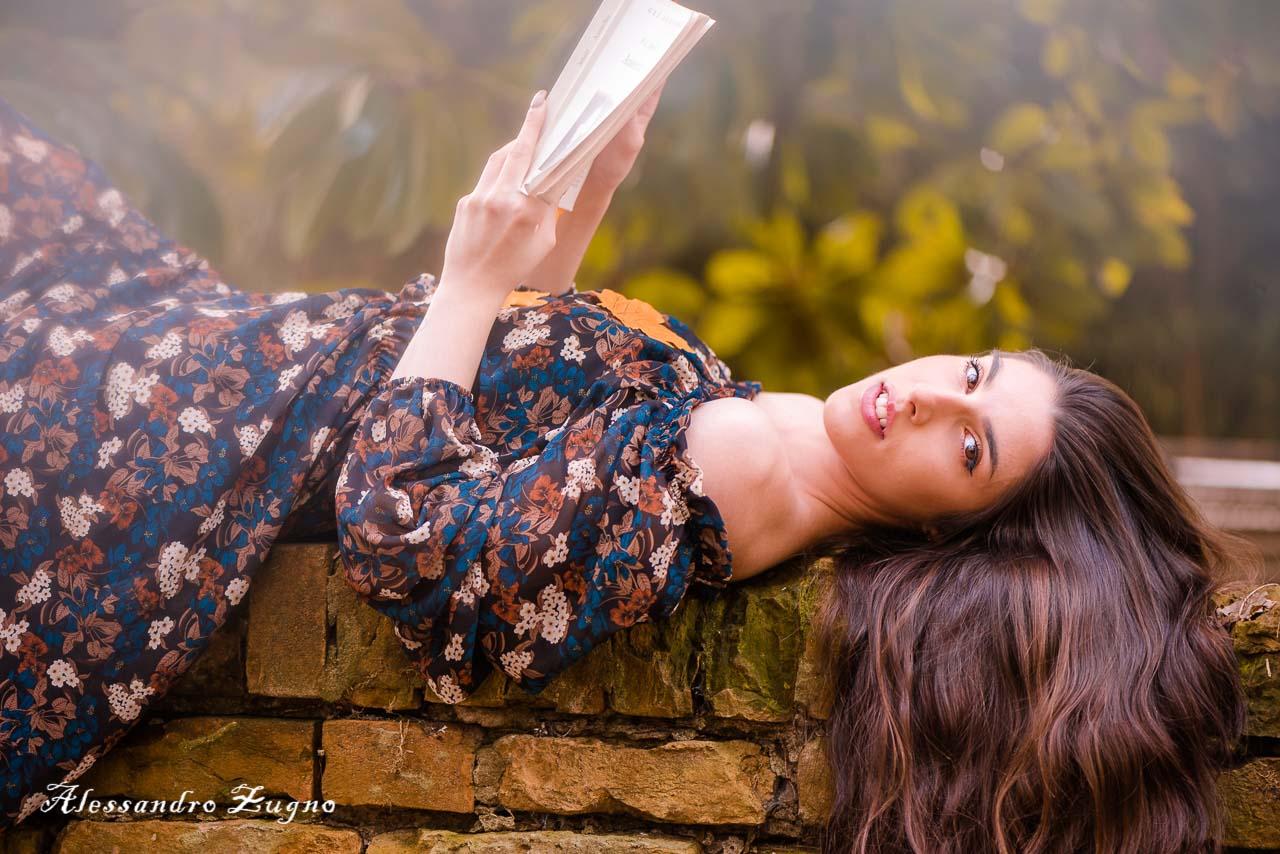 ragazza distesa su un muretto mentre posa per book fotografico autunnale